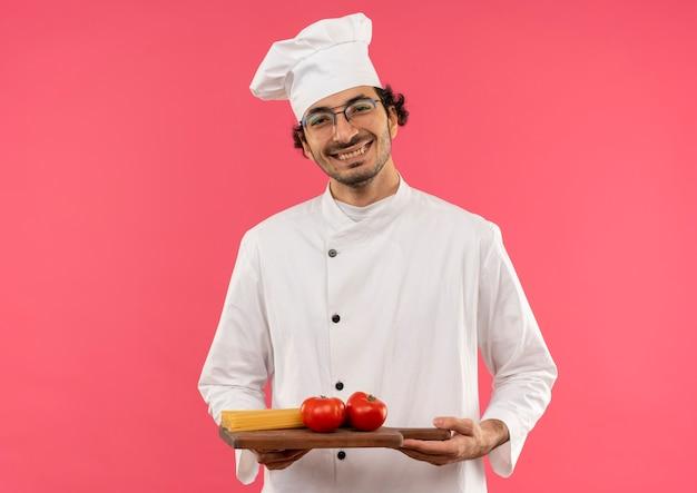 Erfreulicher junger männlicher koch, der kochuniform und gläser trägt, die spaghetti mit tomate auf schneidebrett halten, lokalisiert auf rosa wand