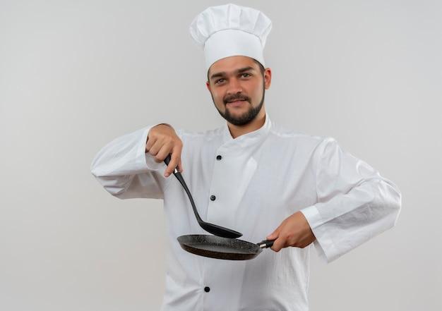 Erfreulicher junger männlicher koch in der kochuniform, die geschlitzten löffel und pfanne lokalisiert auf weißem raum hält