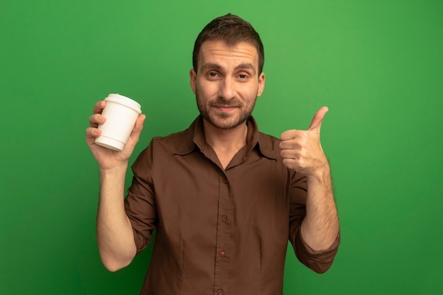 Erfreulicher junger mann, der front betrachtet, die plastikkaffeetasse hält, die daumen oben lokalisiert auf grüner wand zeigt
