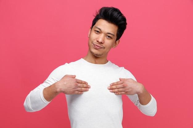 Erfreulicher junger mann, der mit den händen auf sich zeigt