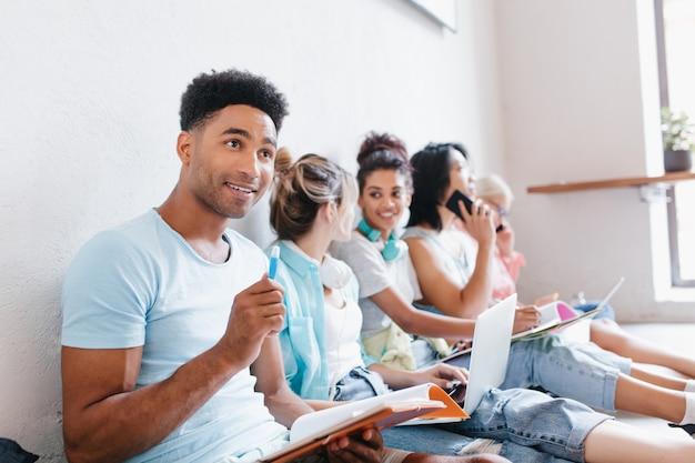 Erfreulicher junger mann mit büchern und lehrbüchern, die mit einem lächeln aufblicken, während seine klassenkameraden etwas besprechen. innenporträt von studenten, die sich auf die prüfung vorbereiten.