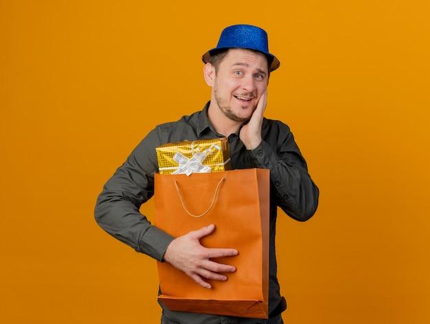 Erfreulicher junger party-typ, der blauen hut trägt, der geschenktüte hält und hand auf wange lokalisiert auf orange legt
