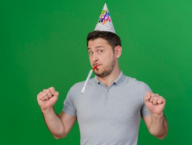 Erfreulicher junger party-typ, der geburtstagskappe trägt, die pfeife zeigt, die ja geste lokalisiert auf grün zeigt