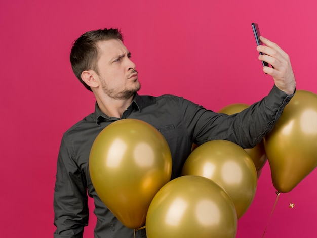 Erfreulicher junger party-typ, der schwarzes hemd trägt, das zwischen luftballons steht und ein selfie isoliert auf rosa nimmt