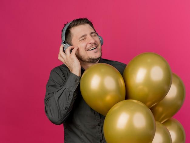 Erfreulicher junger party-typ, der schwarzes hemd und kopfhörer trägt, die luftballons isoliert auf rosa halten