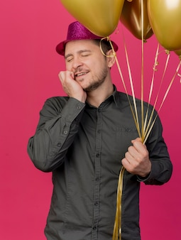 Erfreulicher junger party-typ mit geschlossenen augen, der rosa hut hält, der ballons hält, die hand auf wange lokalisiert auf rosa