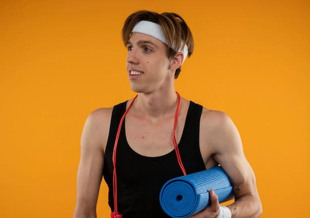 Erfreulicher junger sportlicher kerl, der seite mit springseil am hals betrachtet, der yogamatte lokalisiert auf orange wand hält