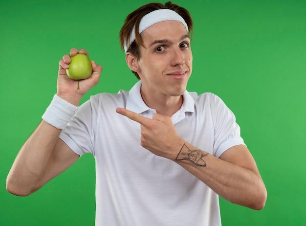 Erfreulicher junger sportlicher kerl, der stirnband mit armband hält und auf apfel lokalisiert auf grüner wand zeigt