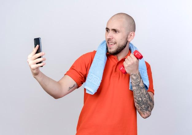 Erfreulicher junger sportlicher mann, der hantel mit handtuch auf schulter hält, nehmen ein selfie lokalisiert auf weißer wand