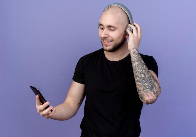Erfreulicher junger sportlicher mann, der kopfhörer trägt und telefon lokalisiert auf purpur hält und betrachtet