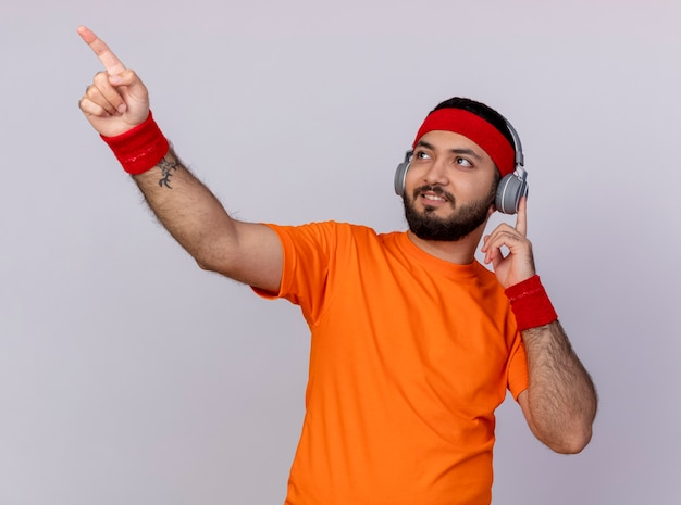 Erfreulicher junger sportlicher mann, der seite betrachtet, die stirnband und armband mit kopfhörerspitzen trägt