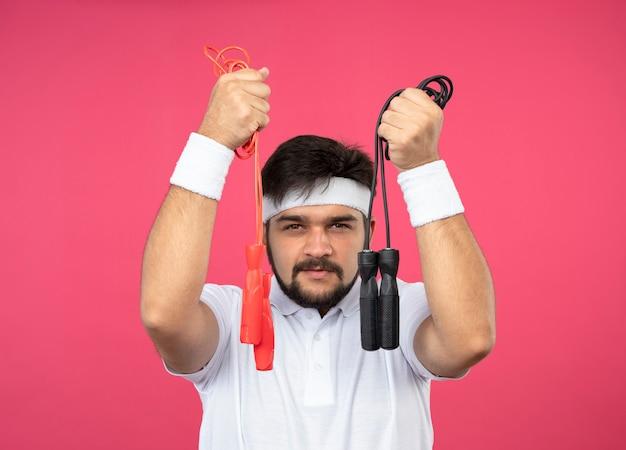 Erfreulicher junger sportlicher mann, der stirnband und armband hält, die springseile halten, die auf rosa wand lokalisiert werden