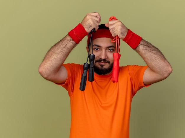 Erfreulicher junger sportlicher mann, der stirnband und armband hält, die springseile um gesicht lokalisiert auf olivgrünem hintergrund halten