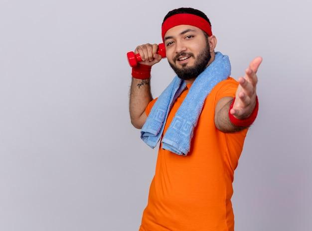 Erfreulicher junger sportlicher mann, der stirnband und armband hält hantel mit handtuch auf schulter hält