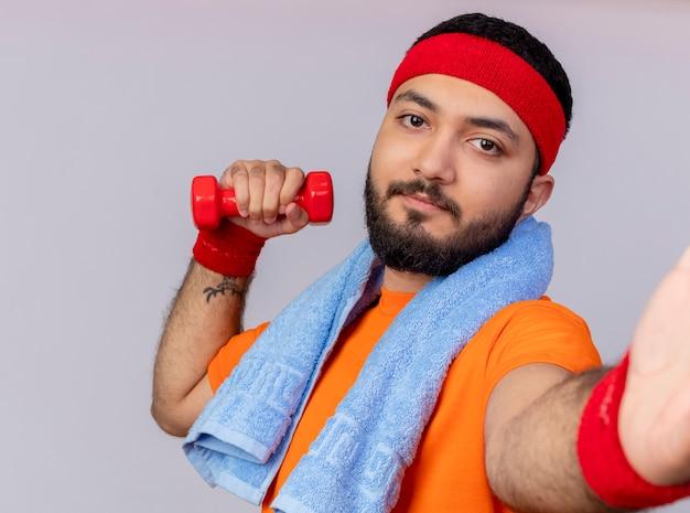 Erfreulicher junger sportlicher mann, der stirnband und armband hält kamera hält, die mit hantel mit handtuch auf schulter lokalisiert auf weißem hintergrund ausübt