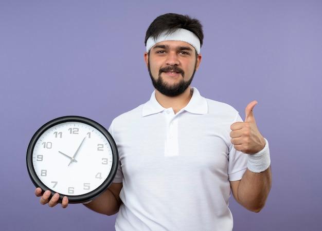 Erfreulicher junger sportlicher mann, der stirnband und armband hält wanduhr, die daumen oben zeigt