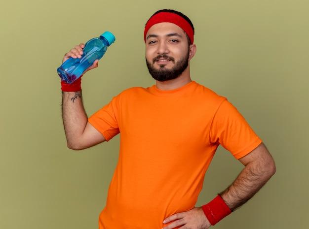 Erfreulicher junger sportlicher mann, der stirnband und armband hält wasserflasche hält und hand auf hüfte lokalisiert auf olivgrün legt