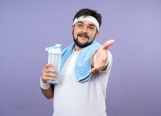 Erfreulicher junger sportlicher mann, der stirnband und armband hält wasserflasche mit handtuch auf schulter hält hand hält