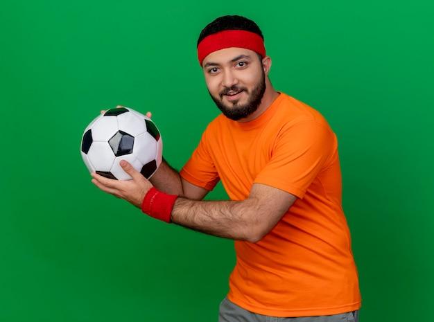 Erfreulicher junger sportlicher mann, der stirnband und armband trägt, hält ball an der seite lokalisiert auf grünem hintergrund