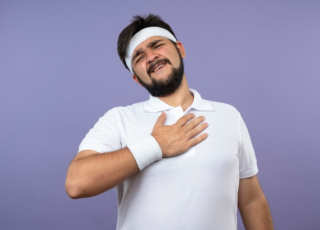 Erfreulicher junger sportlicher mann, der stirnband und armband trägt und hand auf brust legt