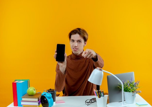 Erfreulicher junger studentenjunge, der am schreibtisch mit schulwerkzeugen sitzt, die telefon halten und ihnen geste zeigen, die auf gelber wand lokalisiert wird