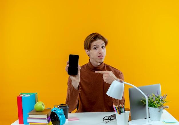 Erfreulicher junger studentjunge, der am schreibtisch mit den schulwerkzeugen hält und auf telefon lokalisiert auf gelber wand hält