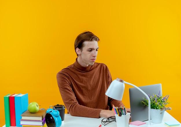 Erfreulicher junger studentjunge, der am schreibtisch mit schulwerkzeugen sitzt, benutzte laptop auf gelb