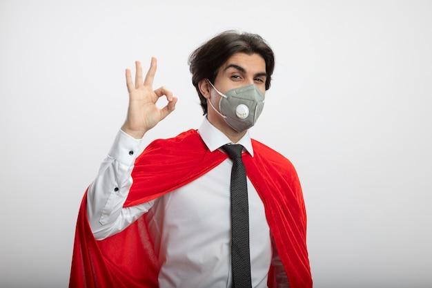 Erfreulicher junger superheld, der krawatte und medizinische maske trägt und okay geste zeigt, die auf weißem hintergrund lokalisiert wird