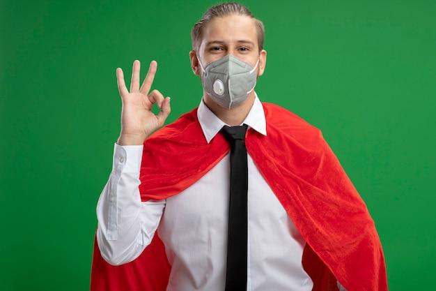 Erfreulicher junger superheld, der medizinische maske und krawatte trägt, die auf grünem hintergrund isolierte okay-geste zeigt