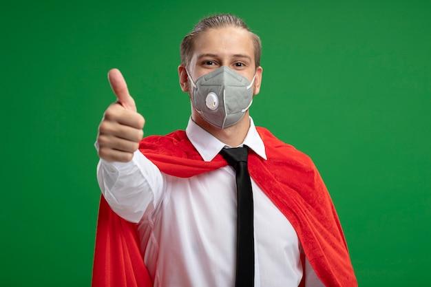 Erfreulicher junger superheld, der medizinische maske und krawatte trägt, die daumen auf grün lokalisiert zeigt