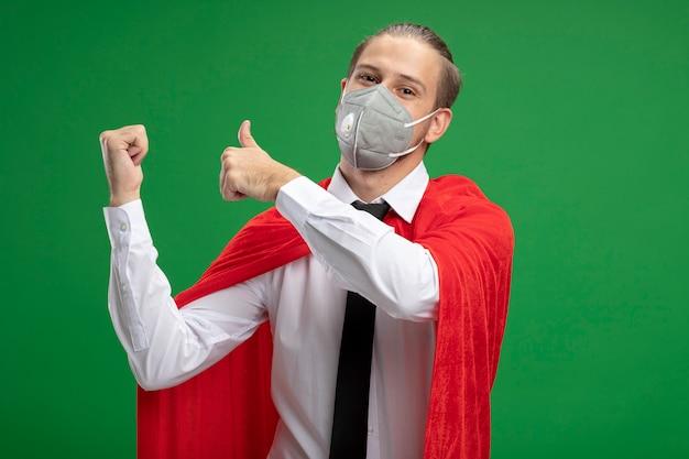 Erfreulicher junger superheld, der medizinische maskenpunkte auf der rückseite trägt, lokalisiert auf grün