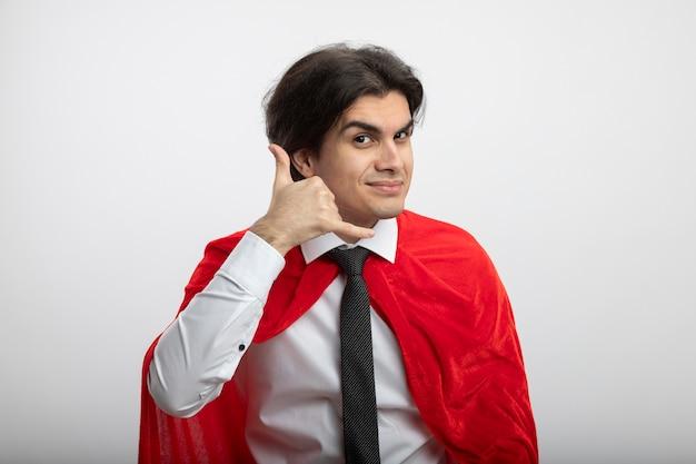 Erfreulicher junger superheld kerl, der kamera betrachtet krawatte zeigt telefonanrufgeste lokalisiert auf weiß