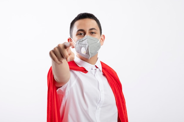 Erfreulicher junger superheldenjunge im roten umhang, der schutzmaske trägt und auf kamera lokalisiert auf weißem hintergrund mit kopienraum schaut