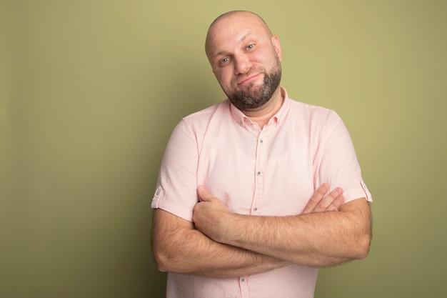 Erfreulicher kahler mann mittleren alters mit kippendem kopf, der ein rosa t-shirt trägt und die hände kreuzt
