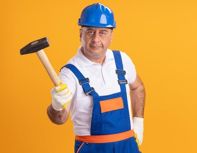 Erfreulicher kaukasischer erwachsener baumeister in uniform, der schutzhandschuhe trägt, hält hammer auf orange