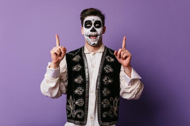 Erfreulicher kaukasischer mann in der mexikanischen kleidung, die für partei vorbereitet. enthusiastisches männliches modell mit halloween-make-up lustiges aufstellen auf lila wand.