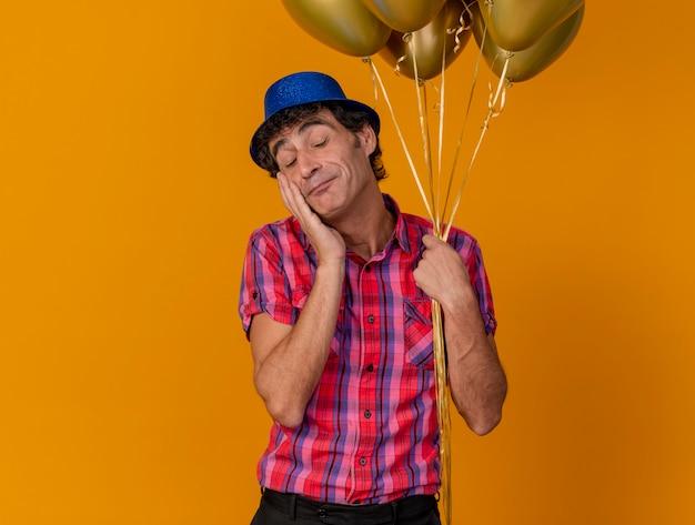 Erfreulicher kaukasischer parteimann mittleren alters, der partyhut hält, der ballons hält, die gesicht mit geschlossenen augen berühren, lokalisiert auf orange hintergrund mit kopienraum