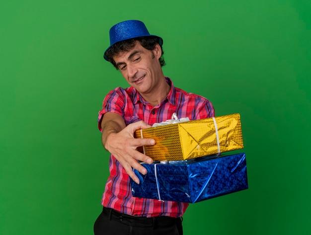 Erfreulicher kaukasischer parteimann mittleren alters, der partyhut trägt, der geschenkverpackungen in richtung kamera ausdehnt und sie lokalisiert auf grünem hintergrund mit kopienraum betrachtet