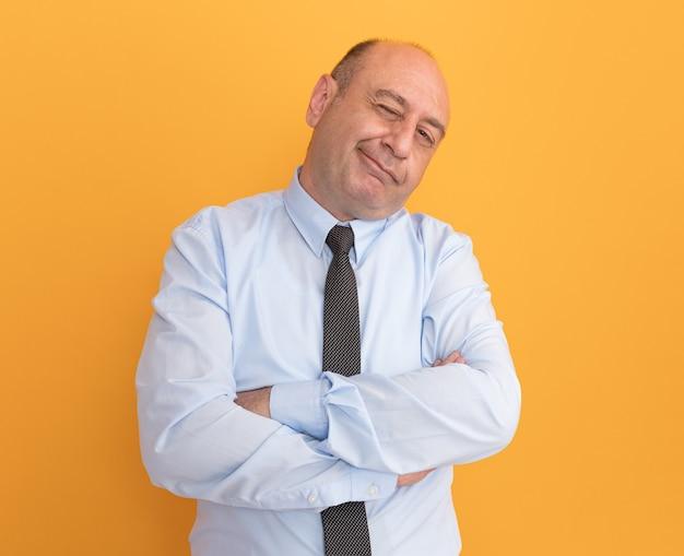 Erfreulicher kippender kopf blinzelte mann mittleren alters, der weißes t-shirt mit krawattenkreuzungshänden trägt, die auf orange wand isoliert sind