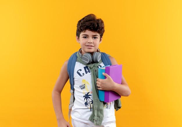 Erfreulicher kleiner schuljunge, der rückentasche und kopfhörer hält bücher hält und hand auf hüfte lokalisiert auf gelbem hintergrund legt