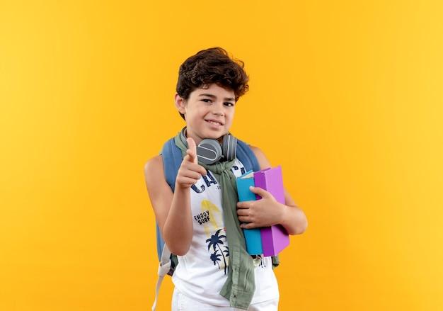 Erfreulicher kleiner schuljunge, der rückentasche und kopfhörer trägt bücher hält und sie geste lokalisiert auf gelbem hintergrund zeigt
