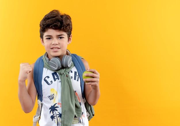 Erfreulicher kleiner schuljunge, der rückentasche und kopfhörer trägt, die apfel halten und ja geste lokalisiert auf gelbem hintergrund mit kopienraum zeigen