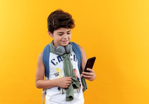 Erfreulicher kleiner schuljunge, der rückentasche und kopfhörer trägt, die telefon lokalisiert auf gelbem hintergrund halten und betrachten