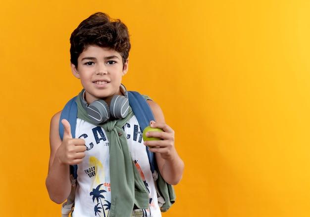 Erfreulicher kleiner schuljunge, der rückentasche und kopfhörer trägt, hält apfel seinen daumen oben lokalisiert auf gelbem hintergrund