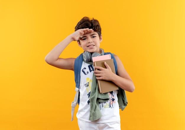 Erfreulicher kleiner schuljunge, der rückentasche und kopfhörer trägt kamera mit hand betrachtet und bücher lokalisiert auf gelbem hintergrund hält