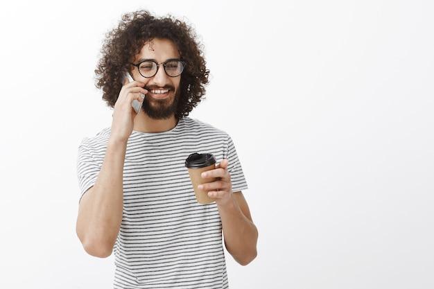 Erfreulicher lässiger freund in t-shirt und brille, der kaffee aus pappbecher trinkt und mit einem leichten lächeln auf dem smartphone spricht und zur seite schaut