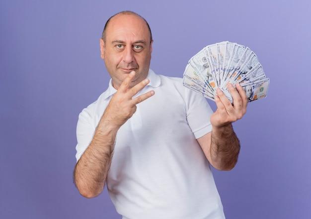 Erfreulicher lässiger reifer geschäftsmann, der geld hält, das seite betrachtet und drei mit hand lokalisiert auf lila hintergrund mit kopienraum zeigt