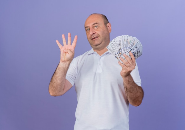 Erfreulicher lässiger reifer geschäftsmann, der geld hält und vier mit hand lokalisiert auf lila hintergrund mit kopienraum zeigt