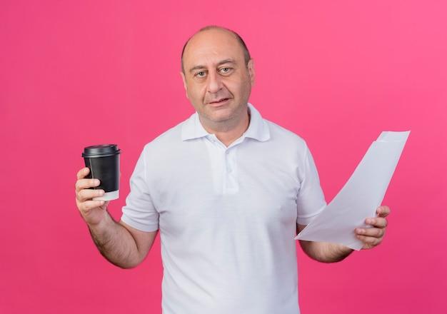 Erfreulicher lässiger reifer geschäftsmann, der plastikkaffeetasse und dokumente lokalisiert auf rosa hintergrund hält