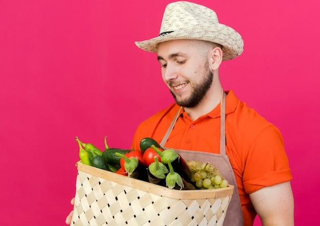 Erfreulicher männlicher gärtner, der gartenhut trägt, hält und schaut auf gemüsekorb
